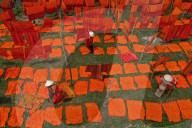 FEATURE -  Arbeiter legen frisch gefärbte Stoffe zum Trocknen in der heissen Sonne aus