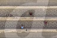 FEATURE - Arbeiter werfen sich gegenseitig Ziegelsteine in einer Fabrik in Bangladesch