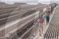 FEATURE - Arbeiter tragen Ziegel durch Felder von Tonziegeln in Bangladesch