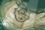 FEATURE - Kajakfahrer treiben über Salzkristall-Formationen im Toten Meer