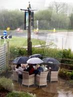 NEWS - Coronavirus: Lassen sich ihr Pint auch nicht vom englischen Wetter vermiesen: Pub Besucher im Regen in Exeter