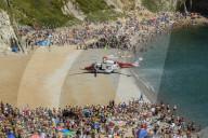 FEATURE - Hubschrauber der Küstenwache landet am vollen Strand von Durdle Door in Dorset