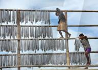 FEATURE - Fischer in Bangladesch hängen auf hohen Gerüsten Fisch zum Trocknen auf