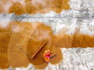 FEATURE - Von kochend heissem Reis steigt Dampf auf, während er von Arbeitern zum Trocknen ausgebreitet wird